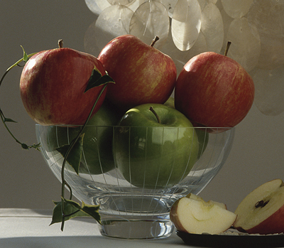 Decorating a fireplace mantel for Christmas with glass bowl and apples