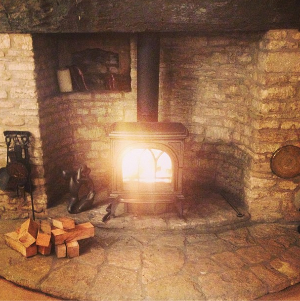 A Gracious Stone Hearth is the Setting for This First Wood Stove Fire of the Season.