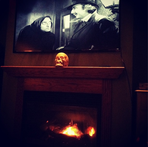 A single, spot-lighted skull, and a scene from a black and white horror movie create a simple but dramatic Halloween mantel