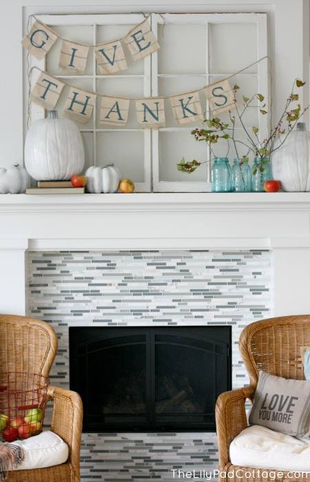 Mason jars and blue lettering on the Thanksgiving banner echo the blue tiles of the fireplace