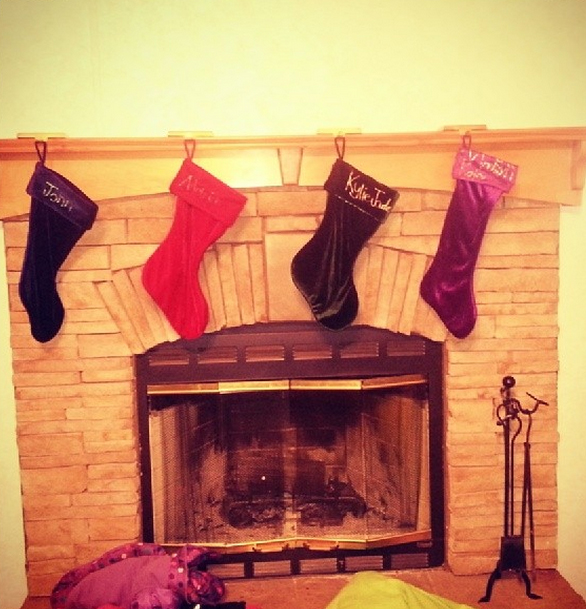 The stockings hanging from the mantel of this arched fireplace await Santa's treats.