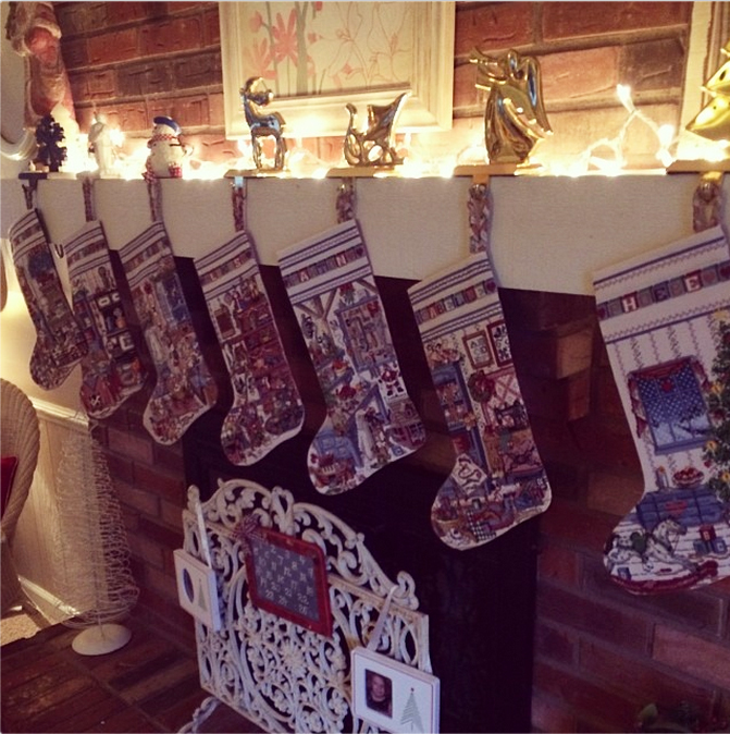 Seven handmade-with-love cross stitched stockings adorn this Christmas mantel.
