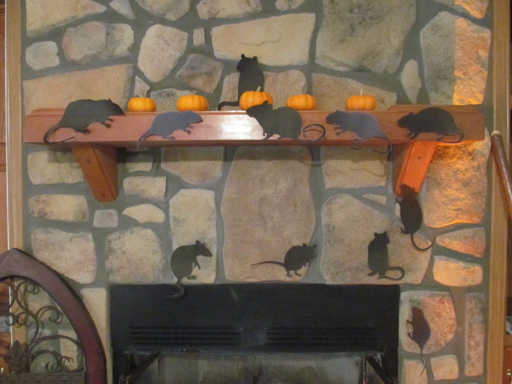 Halloween rats scamper around the fireplace.