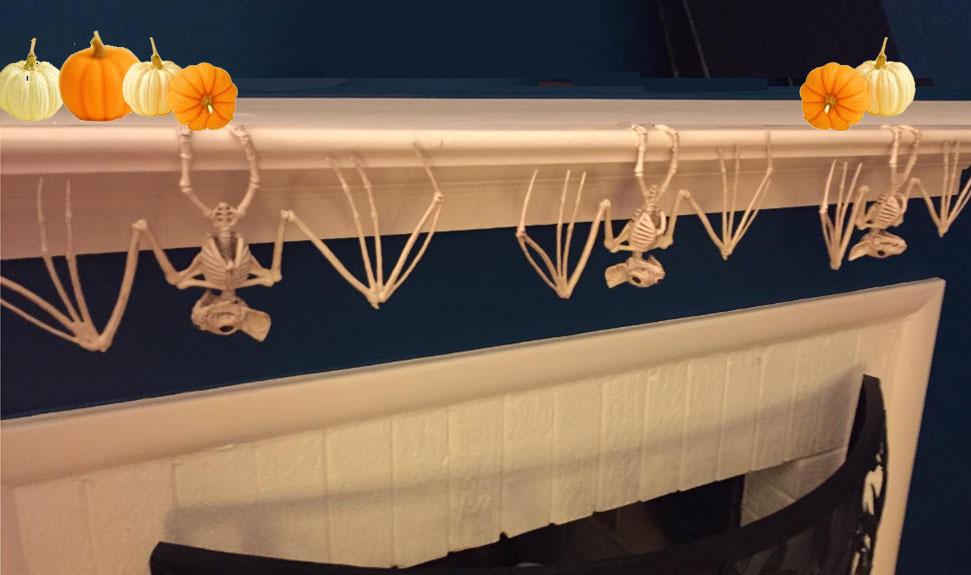 skeleton bats hang on fireplace mantel